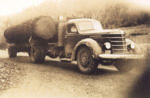A logging truck with a large log on its flatbed. ca 1950