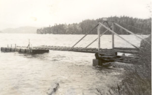 "Wharf and float at Bowen Bay during high tide after Hurricane ""Freida.""  Arbutus Point is in the background. ca.1963"