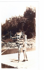 Tommy Huggan standing with a fish on the government dock in Mt. Gardner.  The tea room is visible in the background. ca. 1940's