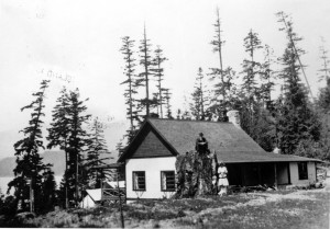 F. Malkin, his wife, and a small child behind their house at King Edward Bay.  J.F. Malkin is sitting on the stump. ca. 1900's