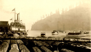 "Terminal Steam Navigation Co. steamer ""Baramba"" at Bowen Island Wharf with log boom in foreground and boats at anchor to the right. ca.1910"